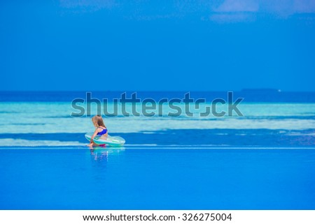 Little adorable girl in outdoor swimming pool on summer vacation - stock photo