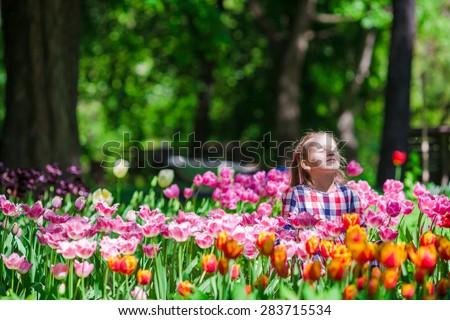 Little adorable girl in the lush garden of tulips - stock photo