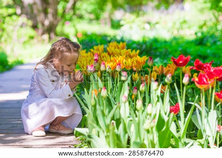 Little adorable girl in tulips garden at warm spring day - stock photo