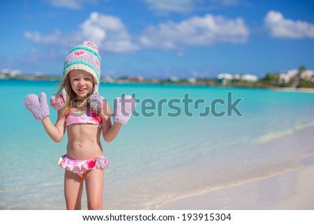 Little adorable girl in warm knitted hat and mittens on a tropical beach