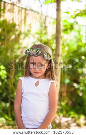 Little adorable girl is playing with butterfly in butterflies garden