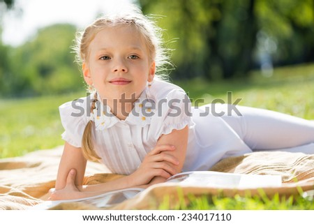 Little adorable girl lying in summer park