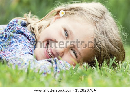 Little adorable girl lying on grass laughing - stock photo