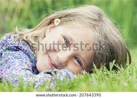 Little adorable girl lying on grass smiling - stock photo