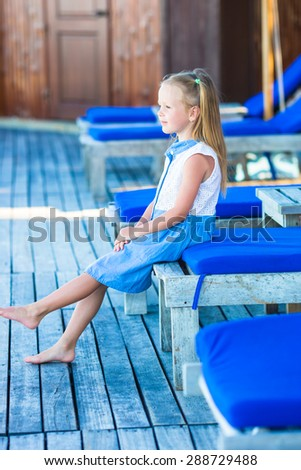 Little adorable girl on beach loungers near the swimming pool - stock photo
