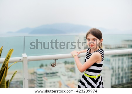Little adorable girl on the balcony enjoing scenic view on the big city and sea - stock photo