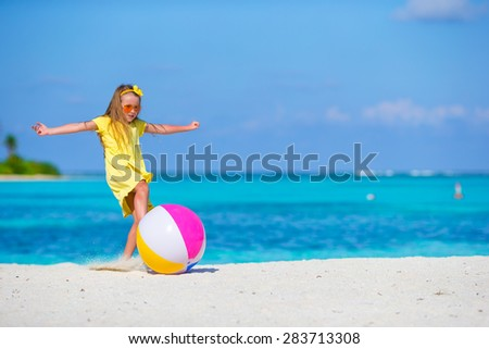 Little adorable girl playing on beach with ball outdoor - stock photo