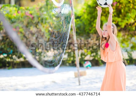 Little adorable girl playing voleyball on beach with ball. Sporty family enjoy beach game outdoors - stock photo