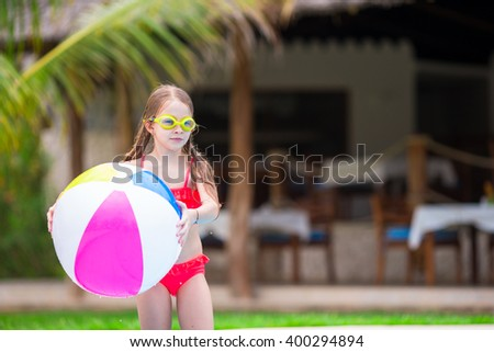 Little adorable girl playing with ball in outdoor swimming pool - stock photo