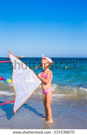 Little adorable girl playing with flying kite on tropical beach - stock photo