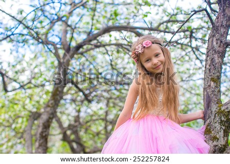 Little adorable girl sitting on blossoming tree in apple garden - stock photo