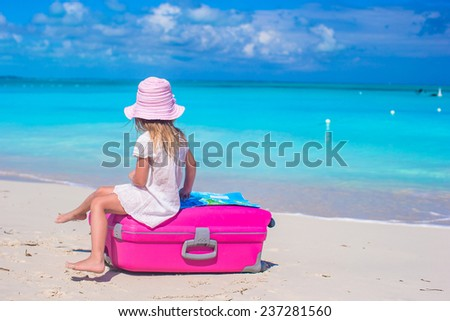 Little adorable girl with big suitcase on tropical beach - stock photo