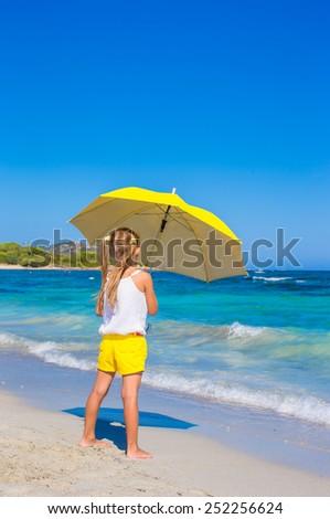 Little adorable girl with big yellow umbrella on tropical beach - stock photo