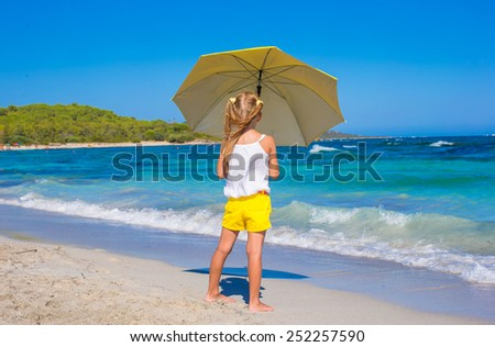 Little adorable girl with big yellow umbrella on tropical beach - stock photo