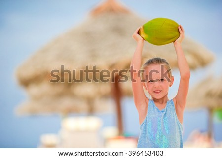 Little adorable girl with coconut on white tropical beach
