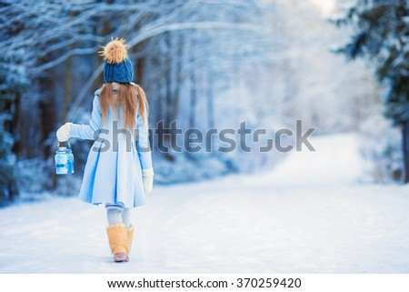 Little adorable girl with in winter day outdoors - stock photo