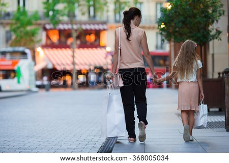 Little adorable girl with mother on shopping in Paris outdoors - stock photo