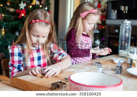 Little adorable girls baking gingerbread house on Christmas eve - stock photo