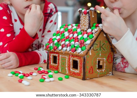 Little adorable girls decorating gingerbread house for Christmas