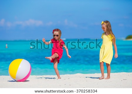Little adorable girls playing with ball on the beach - stock photo