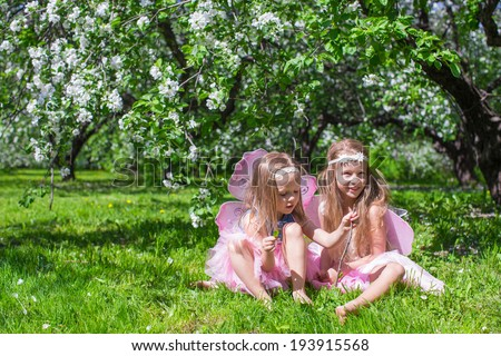 Little adorable girls with butterfly wings in the blossoming apple orchard - stock photo