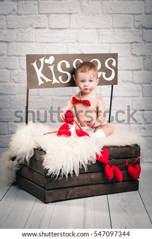 Little adorable kid covered red lipstick kisses