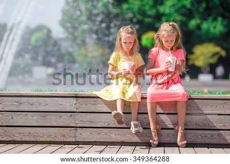 Little adorable kids eating ice cream at summer hot day - stock photo
