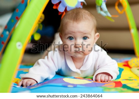 Little adorable newborn infant baby girl lying on tummy on colorful carpet with toys and looking in camera - stock photo