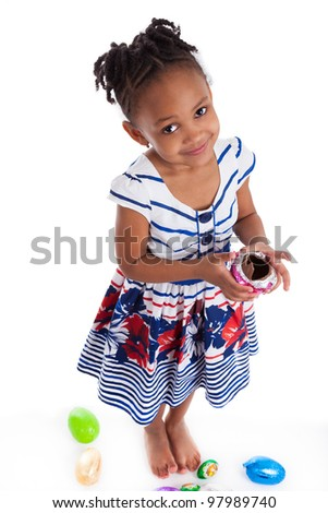 Little african american girl eating chocolate easter egg, isolated on white background - stock photo