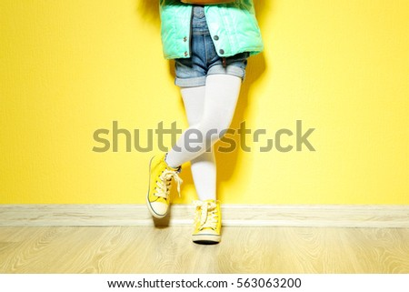 Little African American girl in denim against yellow wall. Fashion concept