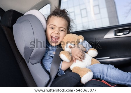 little african american girl with teddy bear sitting in car