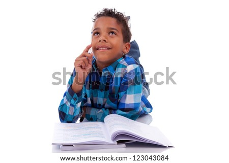 Little african boy lying down on the floor and reading book, isolated on white background - stock photo