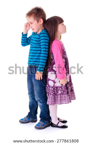 Little aggrieved boy crying and standing near angry girlfriend - stock photo