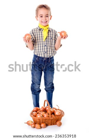 Little agriculturist boy showing the fresh harvested onions - stock photo