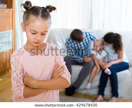 Little American girl sad because of jealous younger sister to parents. focus on girl - stock photo