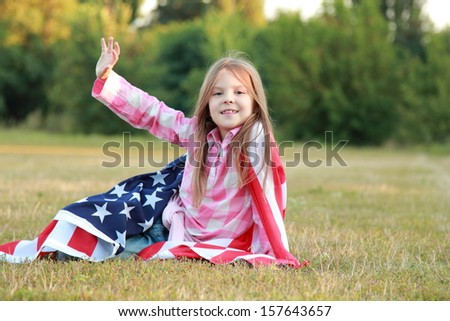 little American in jeans sits on a large American flag and looking into the distance
