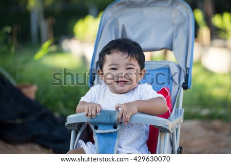 little and very funny boy sitting in the pram and waiting for mom