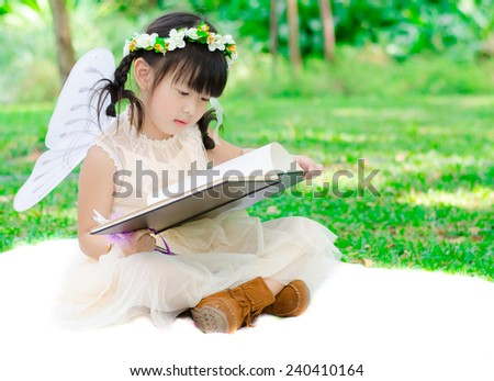 Little angel girl reading a book in the park  - stock photo