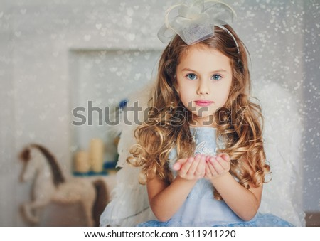Little angel in light blue dress blowing snow to you - stock photo