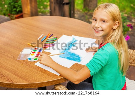 Little artist at work. Top view of cute little girl drawing something on paper and smiling while sitting at the table and outdoors - stock photo