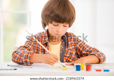 Little artist. Concentrated little boy relaxing while painting with watercolors sitting at the table - stock photo
