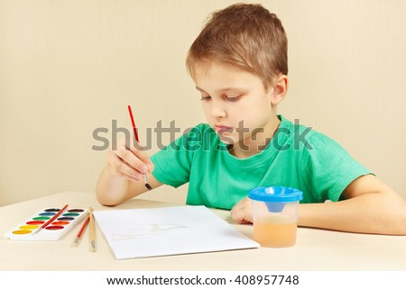 Little artist in a green shirt painting colors - stock photo