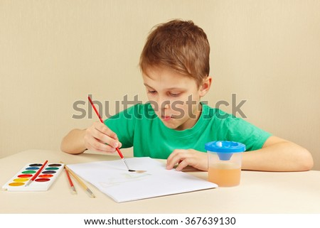 Little artist in a green shirt painting with watercolors - stock photo