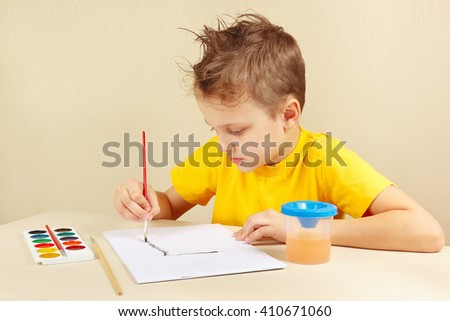 Little artist in a yellow shirt painting colors - stock photo