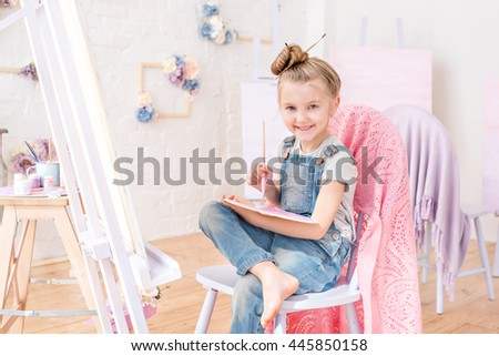 Little artist in denim overalls painting brushes on the easel in her studio