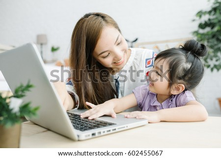 Little Asia Girl Using Digital Laptop E-learning Concept with teacher or mother