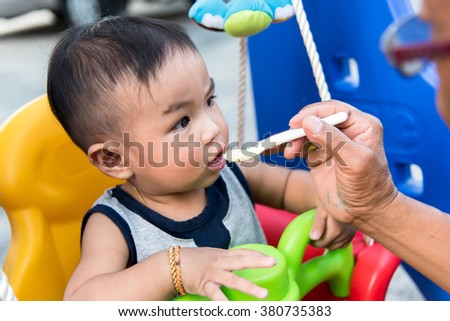 Little Asian baby boy eating rice porridge with father