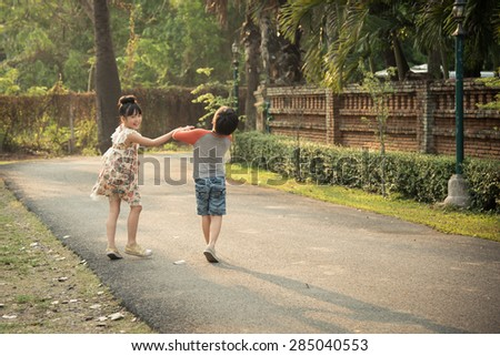 Little asian boy and girl walking under sunrise