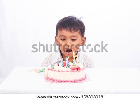 little asian boy blowing birthday cake - stock photo