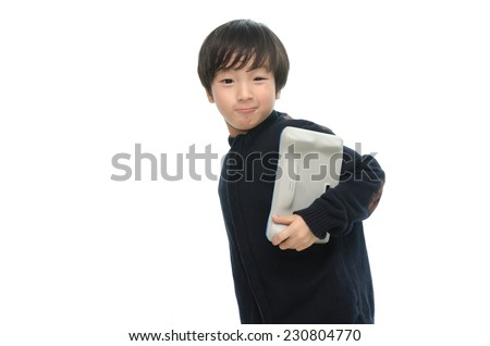 Little asian boy holding tablet on white background isolated